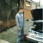 Young car mechanic in light blue overall