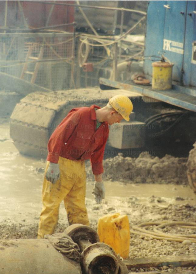 Guy on building site wearing red coveralls, hardhat and yellow waterproof PVC trousers 1