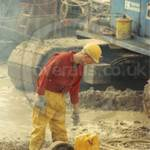 Guy on building site wearing red coveralls, hardhat and yellow waterproof PVC trousers