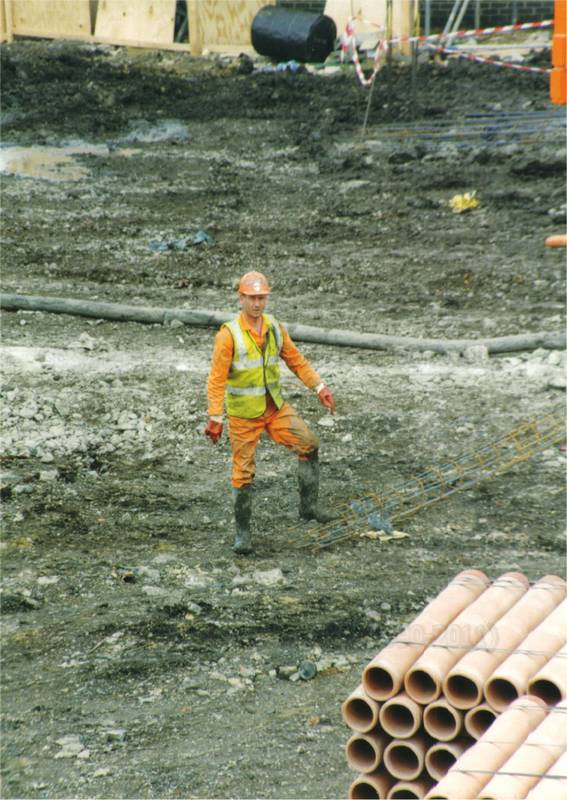Guy drilling wearing orange coveralls & yellow hi-vis waistcoat 1