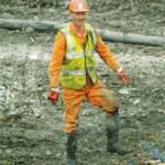 Guy drilling wearing orange coveralls & yellow hi-vis waistcoat