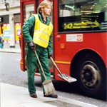 Oliver the road sweeper, wearing green coveralls and yellow hi-vis tabard