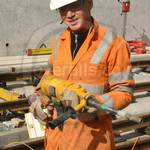 Young lad working on a railway construction site wearing orange hi-vis overalls 15