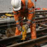 Young lad working on a railway construction site wearing orange hi-vis overalls