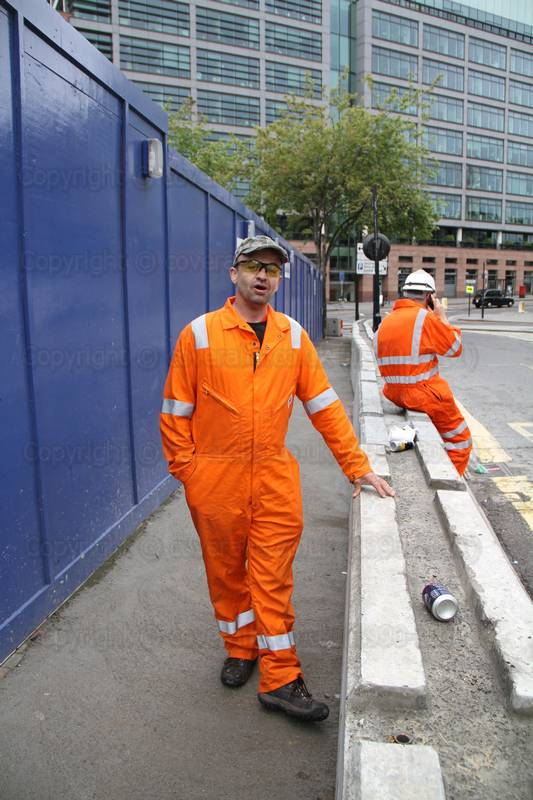 Pest controller working wearing an orange hi-viz pioner riggmaster coverall. Guy wearing an orange hi-viz pioner riggmaster coverall 1