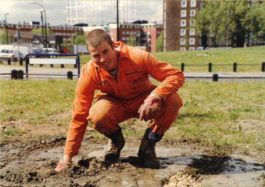 Paul doing some soil drilling, wearing orange coverall, hardhat and mud. Paul drilling wearing orange overalls