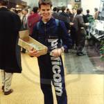 Young Guy in dark blue zip coverall wth large silver lettering down one leg at Cebit Hannover Messe 1994