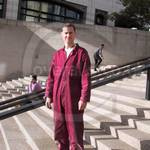 Good looking sexy male Plumber at Canary Wharf wearing maroon coveralls