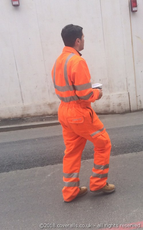 Rail worker wearing Pulsarail Hi-Vis Orange Coverall. Rail worker wearing Pulsarail Rail Spec Orange Combat Coverall 4