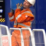 Rail worker wearing a pair of orange Hi-vis Coveralls