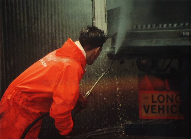Man wearing red waterproof PVC coveralls, power washing an articulated lorry at an industrial truck wash. Truck wash guys in red waterproof PVC overalls and wellies, getting wet 1