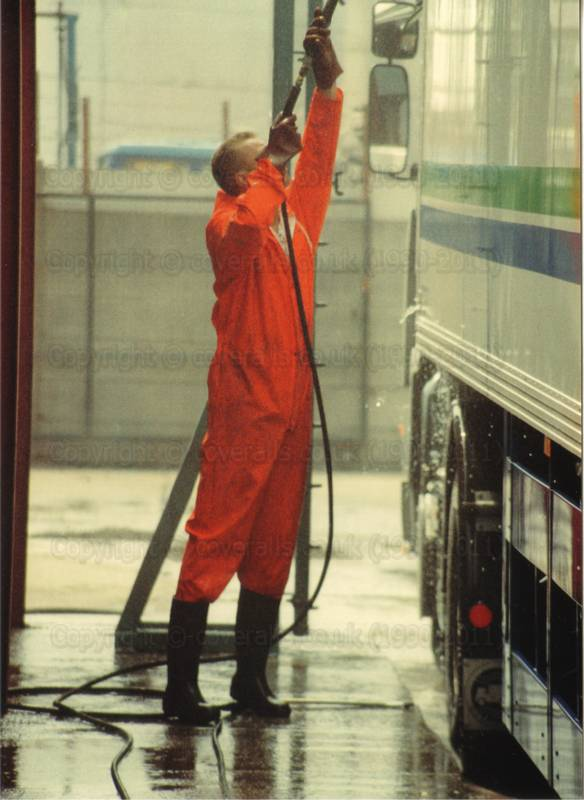 Picture of Man wearing red waterproof PVC coveralls, power washing an articulated lorry at an industrial truck wash