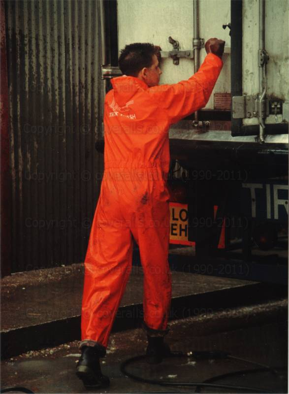 Picture of Man wearing red waterproof PVC coveralls, closing door of articulated lorry at an industrial truck wash