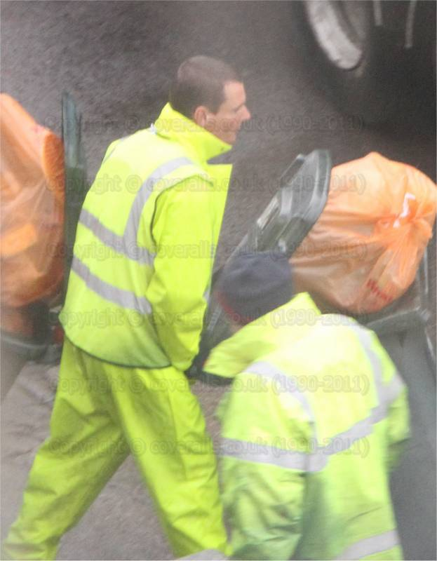 Council refuse workman collecting wheelie bins wearing a yellow pvc coverall in order to keep dry in the rain. Refuse workman in yellow pvc coverall 1