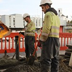 Road Workers digging up the road for new power cabling in their dirty hi-vis portwest Bizflame coveralls