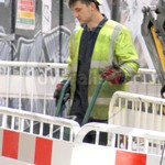 Road worker wearing blue coveralls, yellow hi-vis jacket and white hard hat
