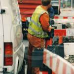 Road digger, wearing orange coveralls and hi-vis fluorescent vest