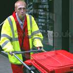 Young lad working as a road sweeper in London wearing red hi-vis boilersuit/coverall and yellow hi-vis waistcoat jacket