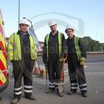 Roader workers wearing blue hi-vis boilersuits and yellow waistcoats