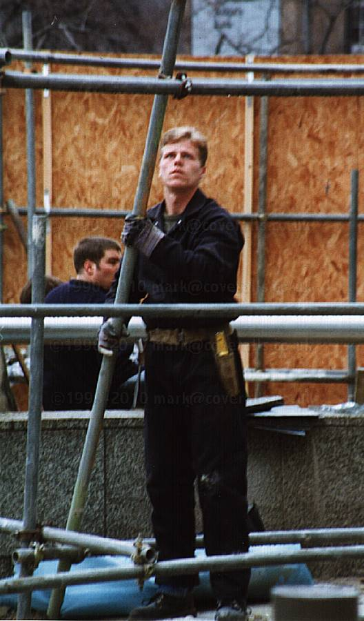 Guy dismantling scaffolding in London, wearing dark blue coveralls 2