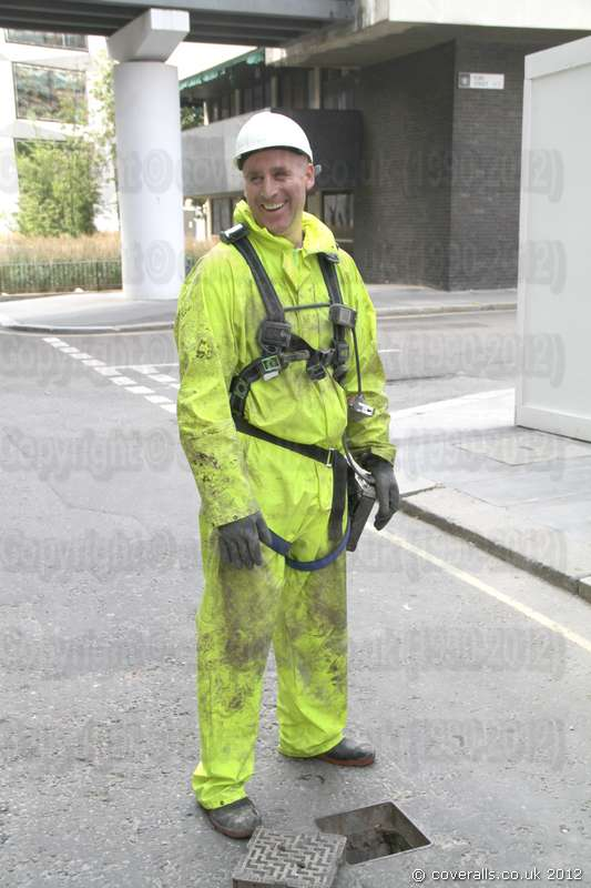Sewer Worker wearing a dirty hi-vis saturn yellow one-piece waterproof PVC coverall suit. Sewer Worker Hi-Vis Saturn Yellow Waterproof PVC Coverall 1