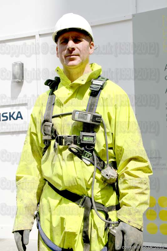 Picture of Sewer Worker wearing a dirty hi-vis saturn yellow one-piece waterproof PVC coverall suit
