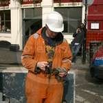Handsome steel construction worker wearing really well worn orange coveralls
