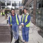 Two young guys at Canary Wharf wearing dirty blue coveralls, yellow hi-vis waistcoats and a white hardhats