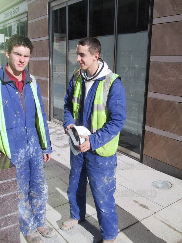 Two young guys at Canary Wharf wearing dirty blue coveralls, yellow hi-vis waistcoats and a white hardhats. Two young guys working at Canary Wharf 7