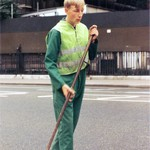 Road Sweeper wearing green coverall and green hi-vis waistcoat