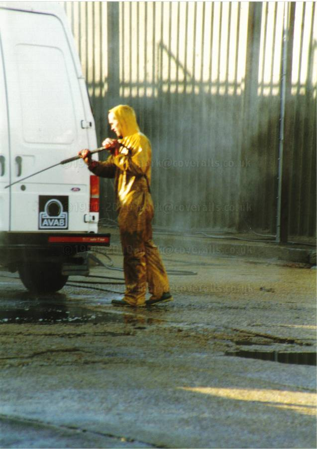 Picture of Young lad working at an industrial truck wash, power washing a van wearing a pair of filthy dirty wet yellow protective PVC coveralls