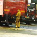 Young lad working at an industrial truck wash, power washing a van wearing a pair of filthy dirty wet yellow protective one-piece PVC coverall suit