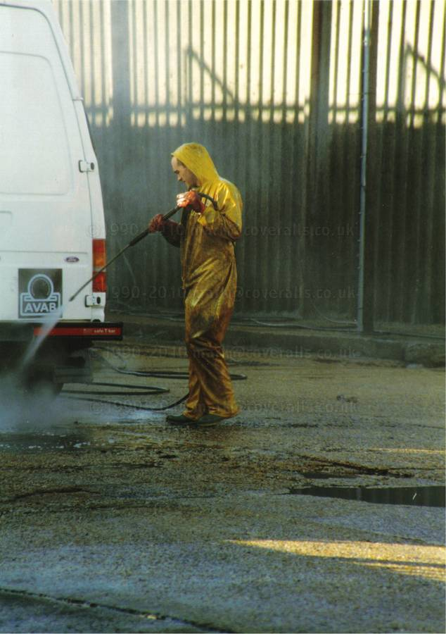Picture of Young lad working at an industrial truck wash, power washing a van wearing a pair of filthy dirty wet yellow protective one-piece PVC coverall suit