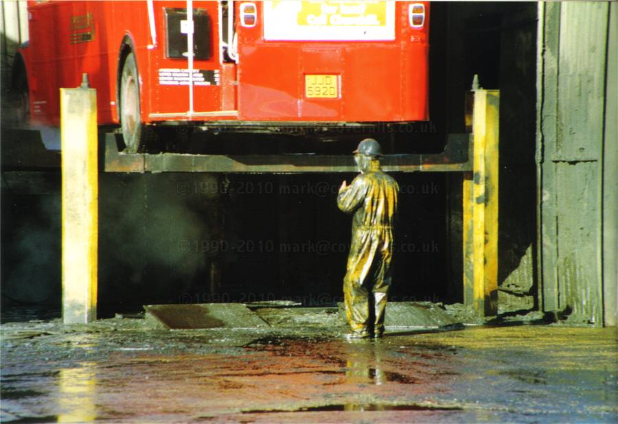 Picture of Young lad working at an industrial truck wash, power washing a bus wearing a pair of filthy dirty wet yellow protective PVC coveralls