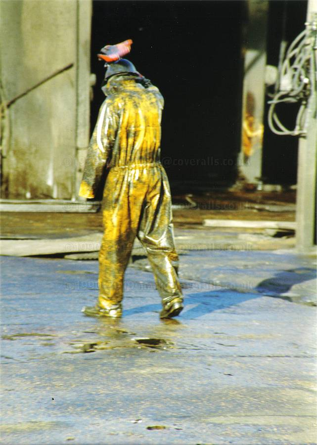 Picture of Young lad working at an industrial truck wash, wearing a pair of filthy dirty wet yellow protective PVC coveralls