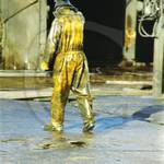 Young lad working at an industrial truck wash, wearing a pair of filthy dirty wet yellow protective PVC coveralls