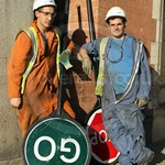 Two young workmen with traffic stop go boards