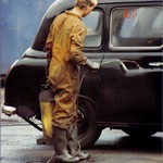 Young lad washing a taxi wearing a pair of dirty brown overalls 1