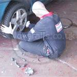 Tyre fitters wearing worn faded boilersuits with tight elasticated waists