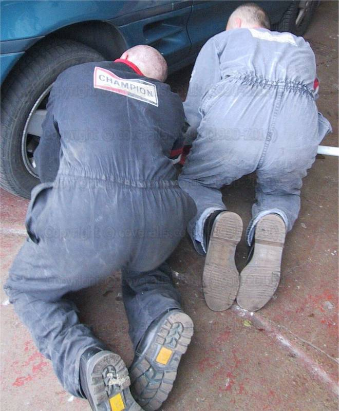 Tyre fitters wearing worn faded boilersuits with tight elasticated waists. Tyre fitters 4