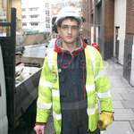 Young lad road digger wearing a blue boilersuit and hi-vis vest, in order to repair an electricity cable