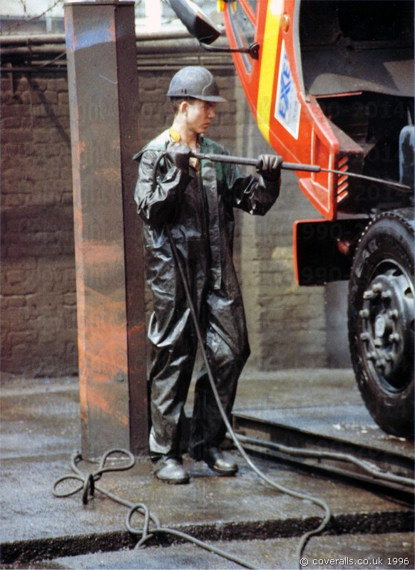 Young lad using a high pressure industrial jet-washer to clean trucks wearing a dirty green waterproof PVC coverall. Truck Washers, wearing dirty green waterproof PVC coveralls 10