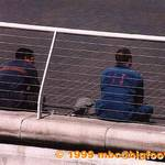 Two workers wearing overalls, taken across a dock
