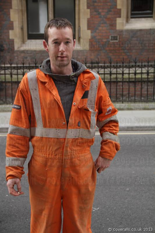 Irish Welder lad working on a building construction site in London wearing a pair of orange Hi-vis Nexus Zero Flame coveralls. Welder lad wearing Orange Hi-vis Nexus Zero Flame Welding Coveralls 2