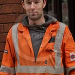Irish Welder lad working on a building construction site in London wearing a pair of orange Hi-vis Nexus Zero Flame coveralls