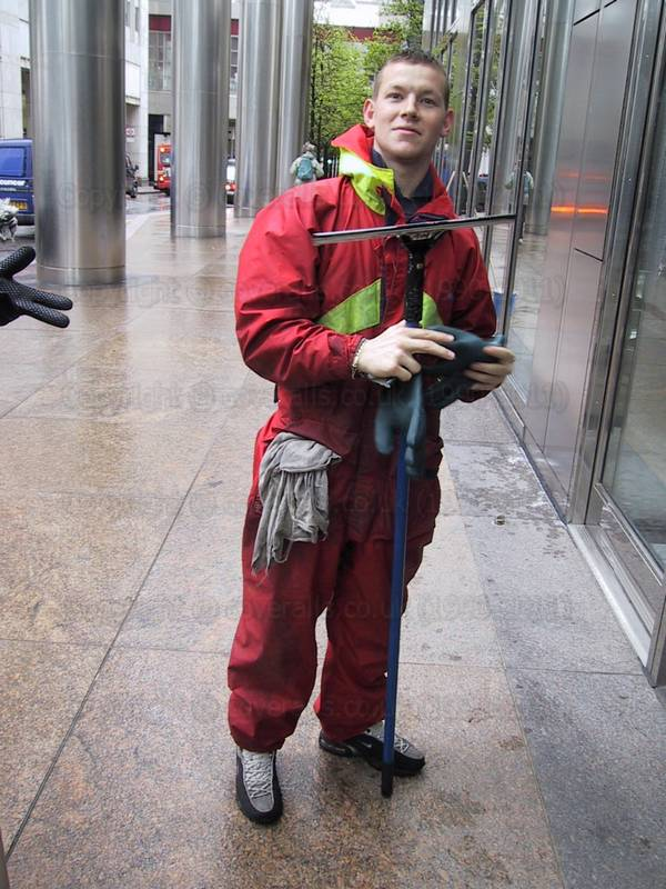 Young lad wearing a red/yellow waterproof coverall, cleaning office windows. Window cleaner wearing a waterproof coverall 1