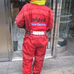 Young lad wearing a red/yellow waterproof coverall, cleaning office windows