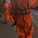 Workmen wearing orange coveralls