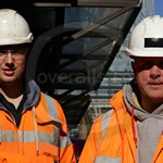 Two workmen working on the crossrail construction project in London in rail spec hi-vis coveralls