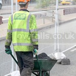 Young lad repairing the road wearing a dirty navy coverall, yellow hi-vis waistcoat and orange hard hat